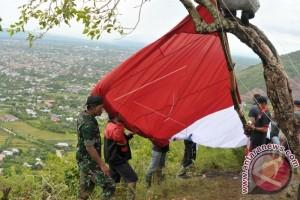 Merah putih raksasa berkibar di puncak bukit