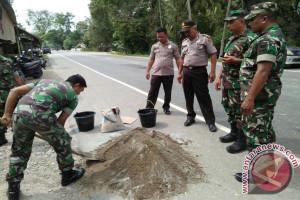 TNIPolri tambal jalan nasional di Aceh Utara