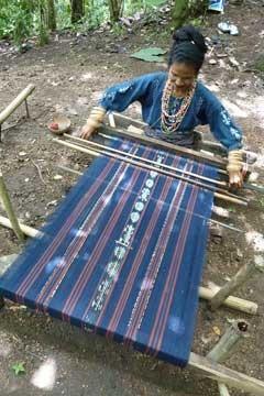 Seorang perajin menyelesaikan pengerjaan kain tenun