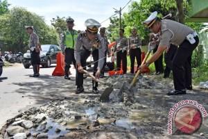 Polisi Tambal Jalan Berlubang