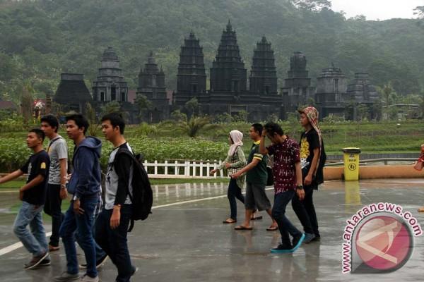 Pengunjung melintas di depan vihara buatan di wahana wisata Jungleland ...