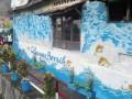 Warga berbincang di dekat tembok rumah dengan gambar Ciliwung Bersih di Kampung Gambar RT 04/09, Kelurahan Babakan Pasar, Bogor Tengah, Kota Bogor, Jawa Barat, Senin (28/11). Kampung padat penduduk yang berdekatan dengan Sungai Ciliwung tersebut secara swadaya dan kreativitas warga masyarakat melukis berbagai gambar tokoh, karakter hewan maupun pemandangan pada dinding dan tembok rumah untuk memberikan kesan indah dan rapih. (ANTARA FOTO/Arif Firmansyah)