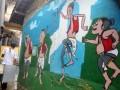 Pedagang melewati tembok rumah yang digambar tokoh pewayangan di Kampung Gambar RT 04/09, Kelurahan Babakan Pasar, Bogor Tengah, Kota Bogor, Jawa Barat, Senin (28/11). Kampung padat penduduk yang berdekatan dengan Sungai Ciliwung tersebut secara swadaya warga melukis berbagai gambar tokoh, karakter hewan maupun pemandangan pada dinding dan tembok rumah untuk memberikan kesan indah dan rapih. (ANTARA FOTO/Arif Firmansyah).