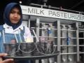 Pramuniaga menunjukkan minuman olahan susu sapi di sebuah restoran Momo Milk, jalan KH. Abdullah Bin Nuh, Kota Bogor, Jawa Barat, Jum'at (16/12). Restoran yang menyajikan makanan dan minuman bersumber dari bahan susu tersebut menggunakan ember mini alumunium sebagai tempat minum layaknya ember susu sapi untuk menarik perhatian pengunjung yang berwisata kuliner ke Kota Bogor. (ANTARA FOTO/Arif Firmansyah/aww/16).