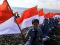 Sejumlah pelajar sata membawa bendera merah putih di Pantai Watu Dodol, Banyuwangi, Jawa Timur. Ratusan siswa pelayaran dan kelautan tersebut merayakan HUT Ke-72 Indonesia tahun 2017 dengan mengibarkan bendera merah putih di pantai. (ANTARA FOTO/Budi Candra Setya/Dok).