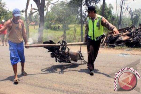 Petugas kepolisian bersama warga membawa satu unit sepeda motor yang