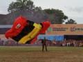 Aksi salah satu dari 10 Anggota Kopassus yang memeriahkan Pembukaan Erau dengan atraksi Terjun Payung mendarat di tengah lapangan Stadion Rondong Demang, Minggu (30/6). (Hayru Abdi/ANTARA Kaltim)