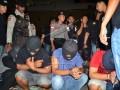 Petugas kepolisian menjaga sejumlah pelaku pengedar narkoba jenis sabu-sabu yang ditangkap di Sulawesi Selatan saat tiba di Pelabuhan Tunon Taka, Kabupaten Nunukan, Kalimantan Utara, Senin (28/12) malam. Sebanyak tujuh anggota komplotan pengedar sabu-sabu tersebut ditangkap atas hasil pengembangan penangkapan tersangka asal Malaysia dengan barang bukti 3,5 kg sabu-sabu pada pekan lalu. ANTARA FOTO/M Rusman