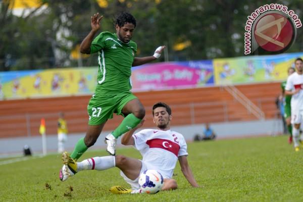 Pesepakbola Iraq Amjed Kalaf Mansoor berusaha merebut bola dari