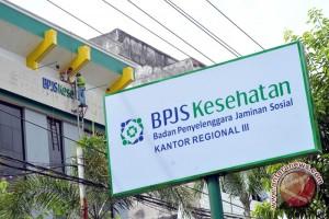 Sejumlah pekerja tengah memasang palakat nama baru BPJS di gedung ...